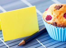 Yellow greeting card near tasty muffin Royalty Free Stock Image