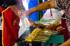 Yellow grilled chicken in stick called pork satay in chacoal bu stock images