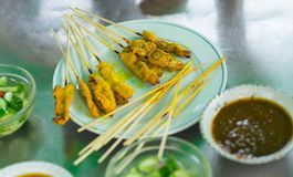 Yellow grilled pork in stick called pork satay in  plate with di. Pping Royalty Free Stock Photo