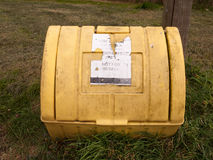 A yellow grit box outside with its lid closed and on the grass n. Ext to a path winter roads salt roads and cars accidents prevention stock images