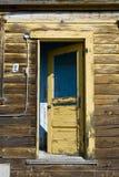 Yellow grunge Door. A yellow peeling door on an abandoned house royalty free stock image