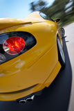 Yellow GTO Sports Coupe Car In Motion. A yellow coupe or 2 door sports car in motion around a corner Stock Images
