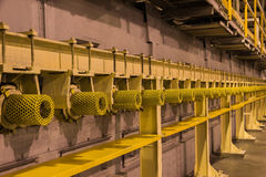 Yellow guard of steel roller shaft for safety in factory. Yellow light background Royalty Free Stock Photography