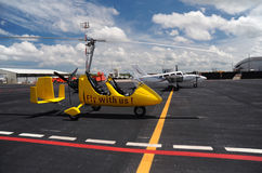 Yellow gyroplane in the international airport Stock Photos