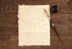 Yellow hand made paper with quill pen and ink on rustic wood tab Royalty Free Stock Images
