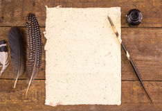 Yellow hand made paper and quill pen on rustic woo Stock Images