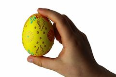 Yellow hand painted easter egg in hand of little child, white background. Interior light Stock Photography