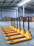 Yellow Hand Pallet Trucks. Couple of yellow hand pallet trucks in the warehouse stock photos