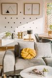 Yellow handmade knot cushion placed on grey couch in white living room interior with crosses and simple posters on the wall stock image