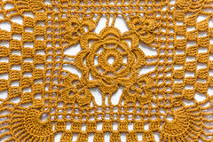 Yellow handmade lace tablecloth texture on white background.  Royalty Free Stock Photography