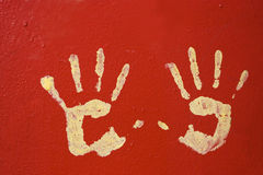 Yellow hands on red wall Royalty Free Stock Photography