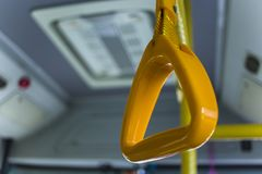 Yellow  hanging handhold for standing passengers in a modern bus. Suburban and urban transport stock images