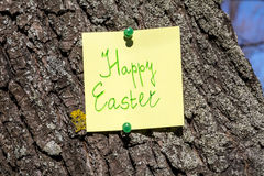 Yellow happy easter paper note  pinned on a tree Stock Photos