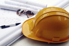 Yellow hard hat. And blueprints (focus on hard hat stock photos