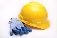 Yellow hard hat. A yellow hard hat and blue gloves Stock Photos