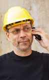 Yellow hard hat. Mature man in yellow hard hat speaking on mobile phone Royalty Free Stock Images
