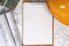 Yellow hard hat and blueprints Stock Image