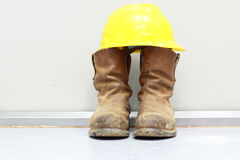 Yellow hard hat and boots Stock Photos