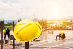 Yellow hard hat on construction site. And building construction background Stock Photos