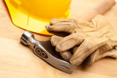 Yellow Hard Hat, Gloves and Hammer on Wood Royalty Free Stock Photo