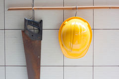 Yellow Hard Hat And Hand Saw Hanging On Tile Wall. Royalty Free Stock Images