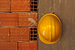 yellow hard hat hanging on concrete wall Stock Photos