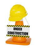 Yellow hard hat on highway traffic cone. Under construction concept background - yellow hard hat on orange highway traffic construction cone with white stripes royalty free stock photos