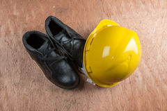 Yellow hard hat and leather boots, protective equipment in construction industry. Royalty Free Stock Image