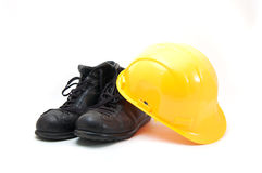 Yellow hard hat and old boots Stock Image