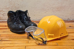 Yellow hard hat, old leather boots and protective goggles Stock Photo