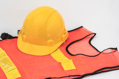 Yellow hard hat and orange and yellow reflective best over white Stock Image