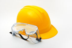 Yellow hard hat and protective goggles Royalty Free Stock Image