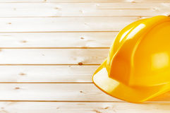 Yellow hard hat on wooden background with copy space Stock Images