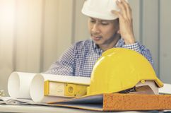 Yellow hard safety helmet hat for safety with engineer team and worker looking paper plans. At construction site stock photography