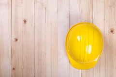 Yellow hardhat architect on brown wood background Stock Images
