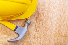 Yellow hardhat and claw hammer on vintage wooden Royalty Free Stock Photos