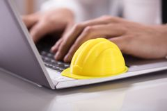 Yellow Hardhat On Laptop Keypad. Close-up Of A Yellow Hardhat On Laptop Keypad Over Desk stock photography