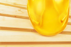 Yellow hardhat on pine wood planks Stock Images