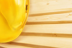 Yellow hardhat on pine wood planks Royalty Free Stock Photography