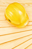 Yellow hardhat on pine wood planks Stock Image