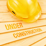 Yellow hardhat on pine wood planks Stock Photography