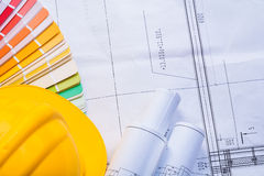 Yellow hardhat rolled white blueprints color Stock Photos