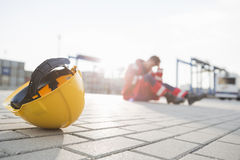 Yellow hardhat at shipyard with depressed male worker in background Stock Image