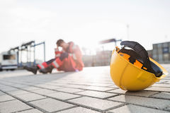 Yellow hardhat at shipyard with depressed male worker in background Royalty Free Stock Images