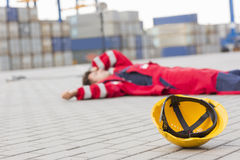 Yellow hardhat at shipyard with depressed male worker lying in shipping yard Stock Image
