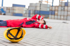 Yellow hardhat at shipyard with depressed male worker lying in shipping yard Stock Photography