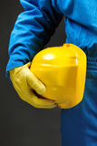 Yellow hardhat under arm Royalty Free Stock Images