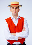 Yellow Hat. Man in yellow hat and red waistcoat standing with folded hands Stock Photo