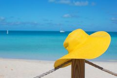Yellow hat on the fence at tropical white beach Royalty Free Stock Image