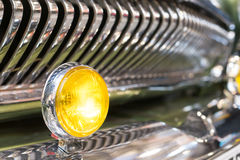 Yellow head light of retro car and radiator grille. Round yellow head light of retro automobile. In background, shiny chrome radiator grille of vehicle, with Royalty Free Stock Photo